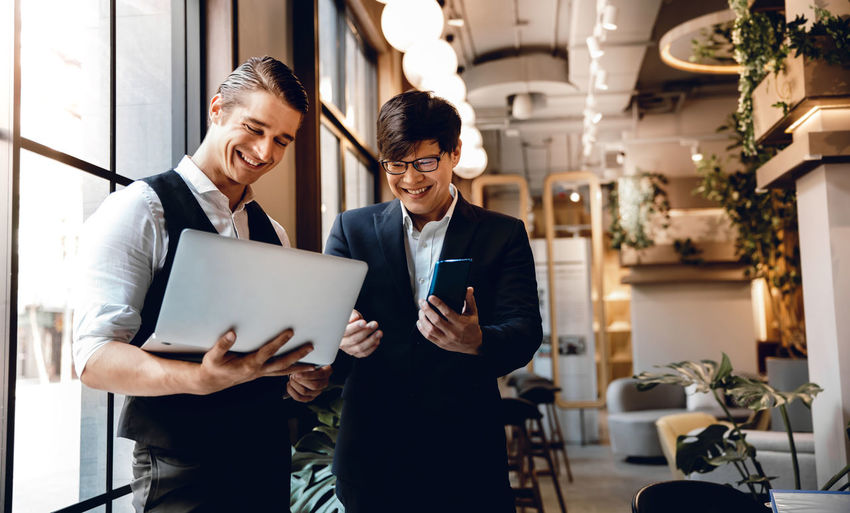 Smiling businessmen looking at laptop in office