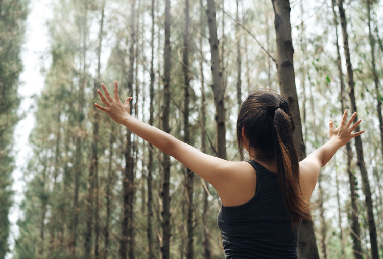 Rear View Of Successful Female Athlete Standing With Arms Outstretched In Forest