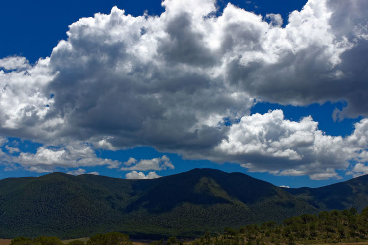 Scenic View Of Mountains Against Stormy Clouds