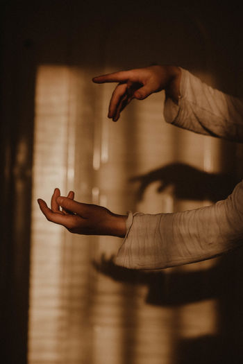 Cropped image of woman hand against curtain in dark room