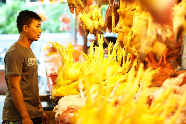 Streetphotography Wetmarket Wetmarketscene Chickens Chicken Leg Butcher Yellow Color Meat! Meat! Meat! Supermarket Quality Working Standing Men Occupation Retail  Business Market For Sale Street Market Farmer Market Retail Display Market Stall Display Stall
