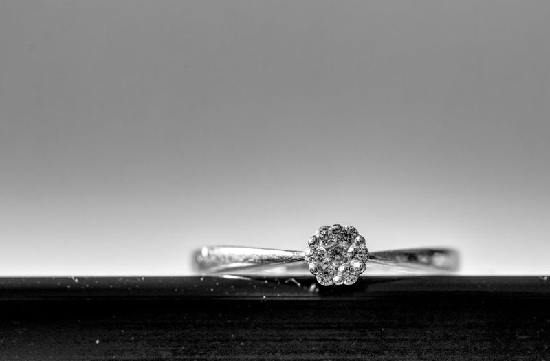 Close-Up Of Diamond Ring On Table Against Gray Background