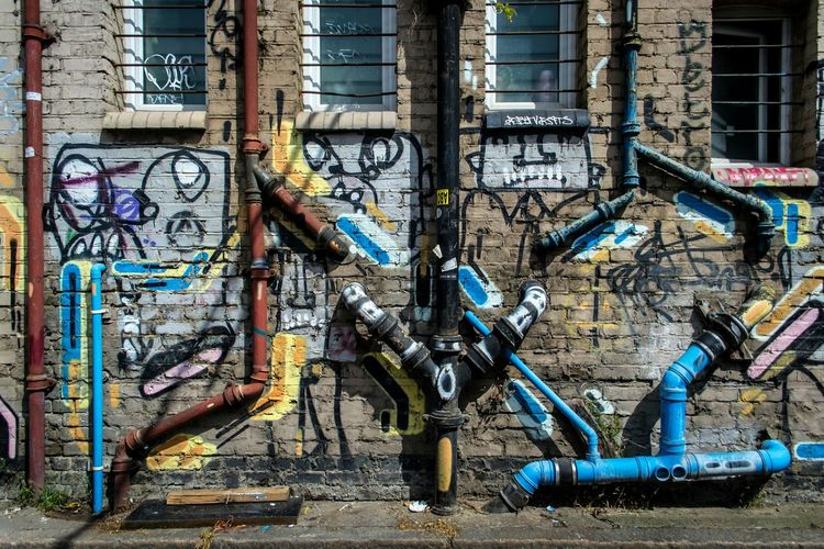Graffiti and pipes on building wall
