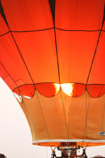 Low angle view of hot air balloon against orange sky
