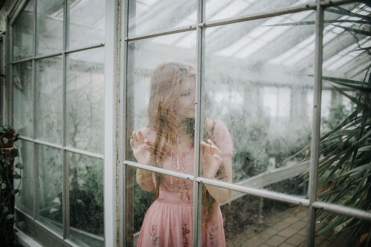 Woman looking through window in greenhouse