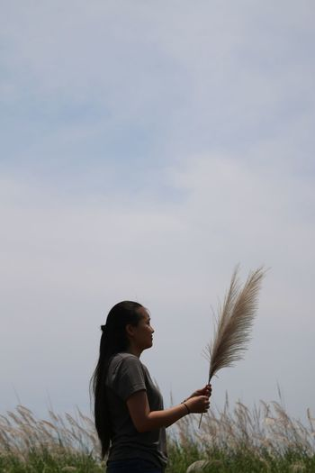 Side View Of Woman Holding Pampas Grass While Standing On Field Against Sky