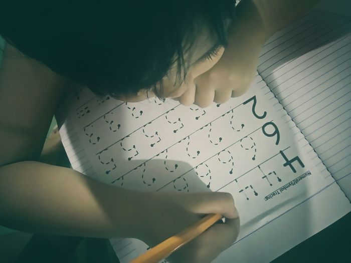 Child writing in book at home