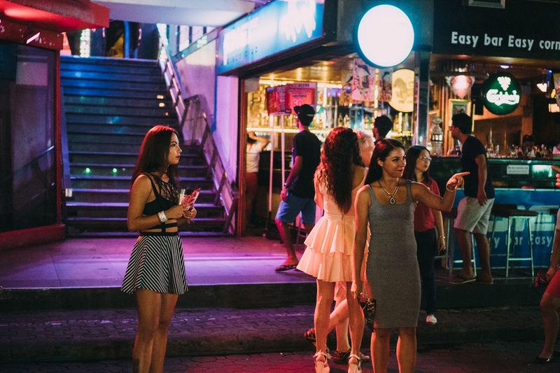 Group of people standing on illuminated street at night