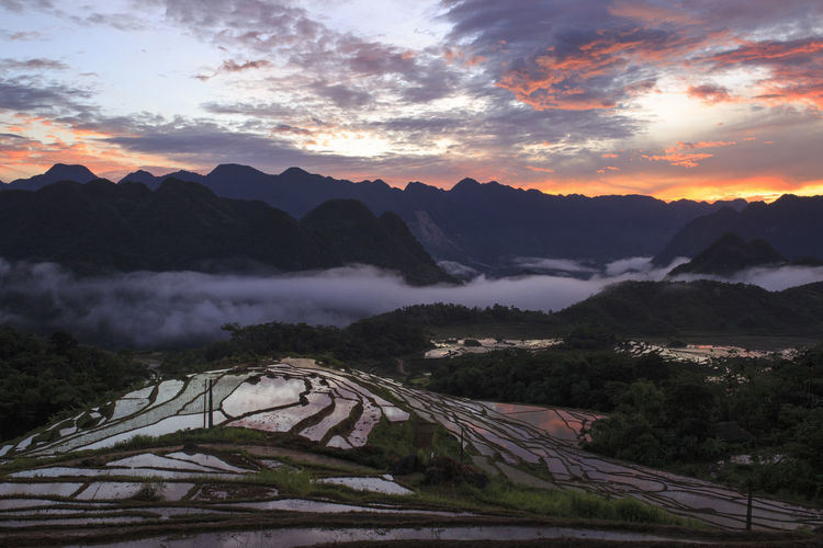 Terraced field by mountains against cloudy sky during sunrise