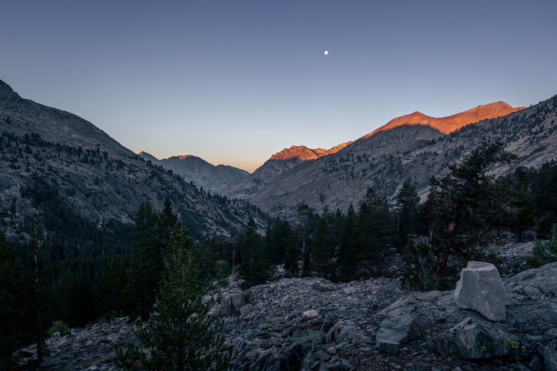 In serenity   JMT DAY 23 - SUNRISE AT SAWMILL PASS JUNCTION Sunrise at Sawmill Pass Junction Soon the sunrise glow descended on the top of the mountains. And no words needed to describe it. The moon was setting slowly, as if it didn't want to. As if it was buying time before it fell into oblivion. The sky was brightening up as the glow got intense. And I thought to myself how blessing witnessing that moment was. I just let everything slip out of my mind in serenity. Sawmill Pass Junction, Kings Canyon National Park, CA Mountain Sky Beauty In Nature Scenics - Nature Moon Tranquility Tranquil Scene Mountain Range Nature Landscape No People Non-urban Scene Idyllic Environment Outdoors Mountain Peak JMT Pct Adventure Sunrise Moon Sunrise Glow
