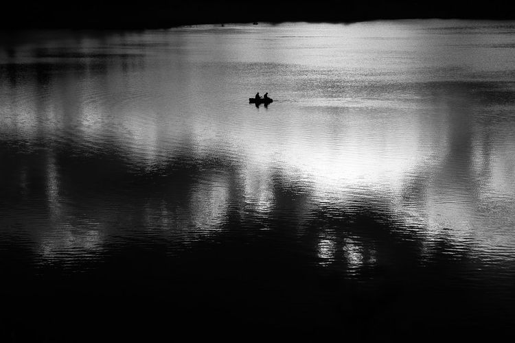 Silhouette people on boat in lake