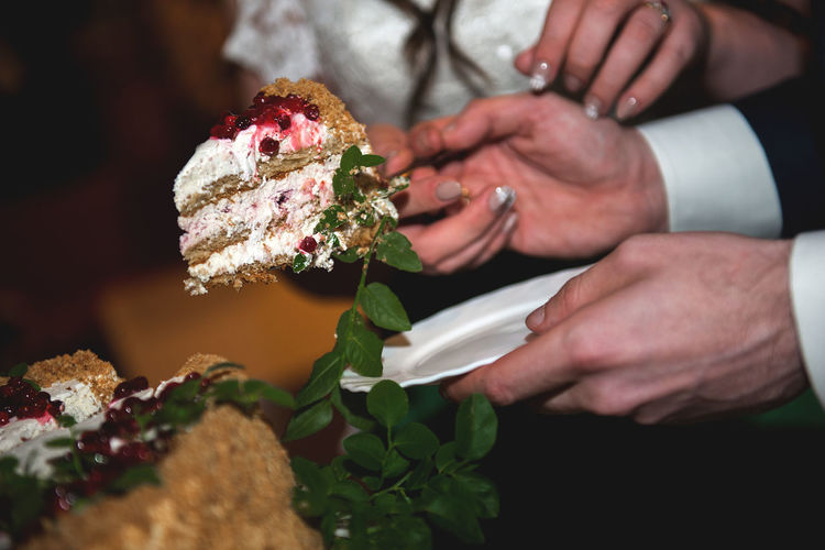 Cropped hands of bride and bridegroom holding wedding cake