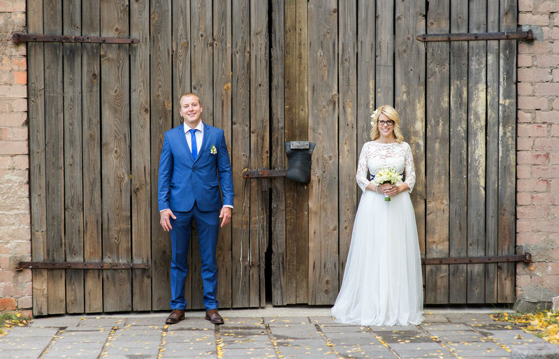 Smiling bridal couple standing against door of barn