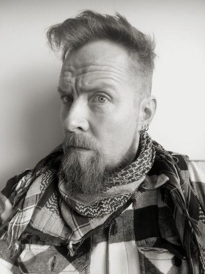 Portrait of bearded man against wall