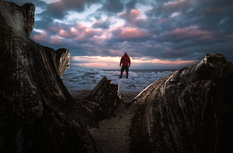 People standing on rock by sea against sky during sunset