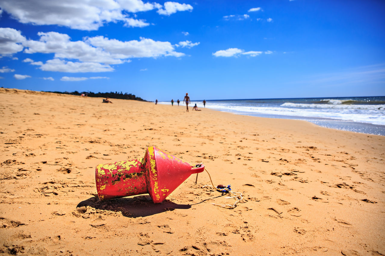Red Buoy On Sand At Beach Blue Sky