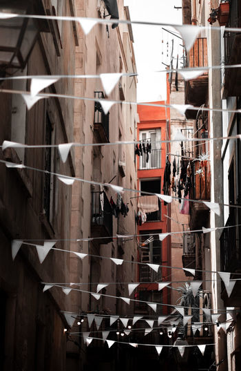 1 of 1.000.000 beautiful narrow alleys you will discover in Barcelona, Spain. Barcelona Catalunya City City Life Narrow SPAIN Alley Architecture Balcony Building Building Exterior Built Structure Day Flags Fujifilm Fujifilm_xseries Grey Sky Hanging No People Outdoors Shadow Street Street Photography Streetphotography White