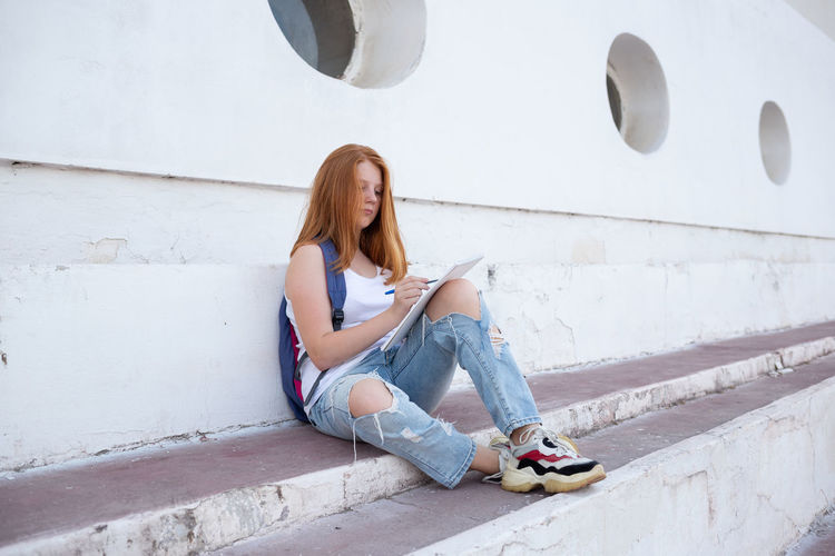 Full length of young woman sitting against wall