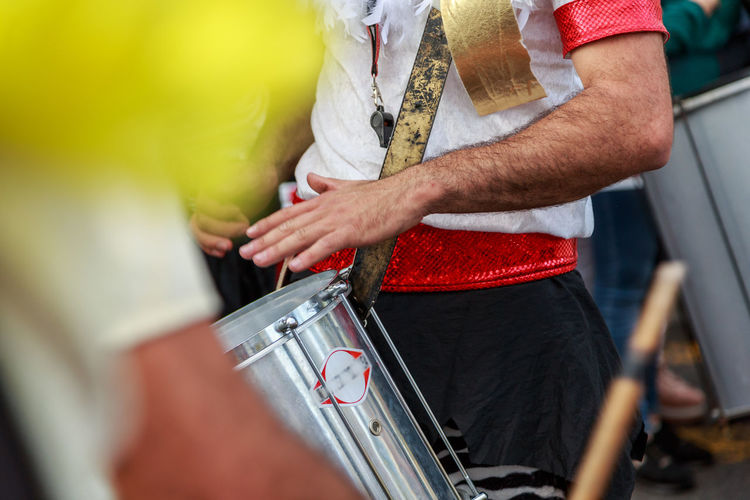 Midsection of man playing drum during festival