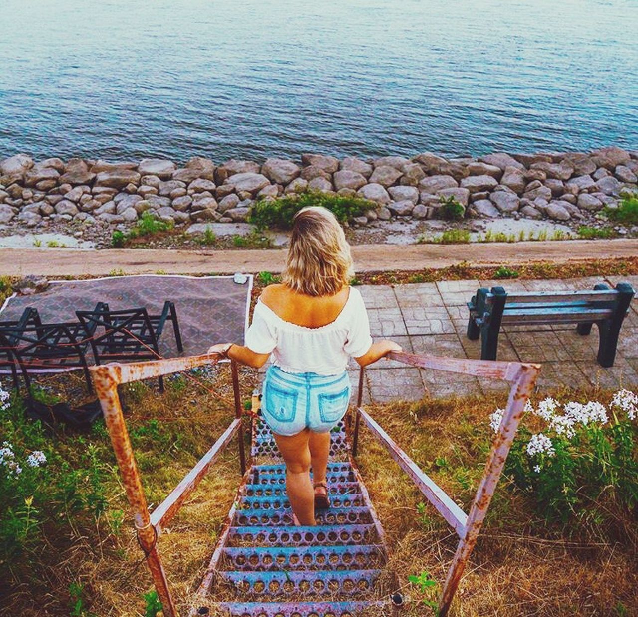 FULL LENGTH REAR VIEW OF WOMAN STANDING ON SEAT BY SEA