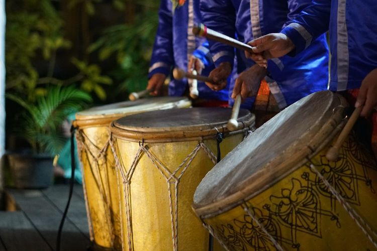 Midsection of men playing drum during event at night