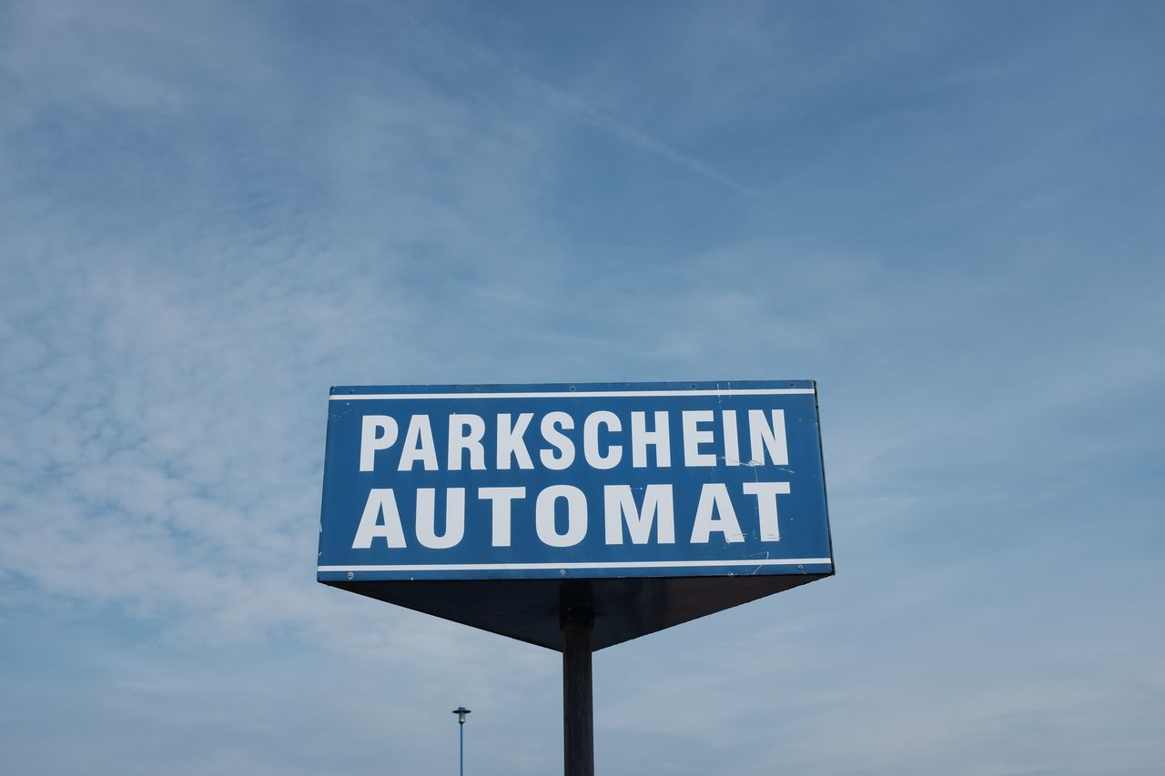text, western script, low angle view, sky, communication, day, blue, no people, cloud - sky, outdoors, road sign, nature, close-up