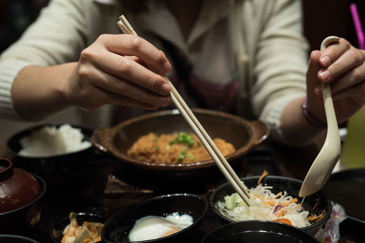 Asian Food Bowl Chinese Food Chopsticks Close-up Focus On Foreground Food Food And Drink Freshness Hand Holding Human Body Part Human Hand Indoors  Kitchen Utensil Lifestyles Midsection One Person Preparing Food Real People Table