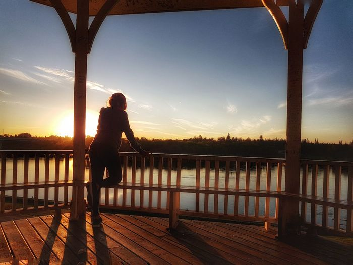 Woman standing in gazebo by river against sky during sunset