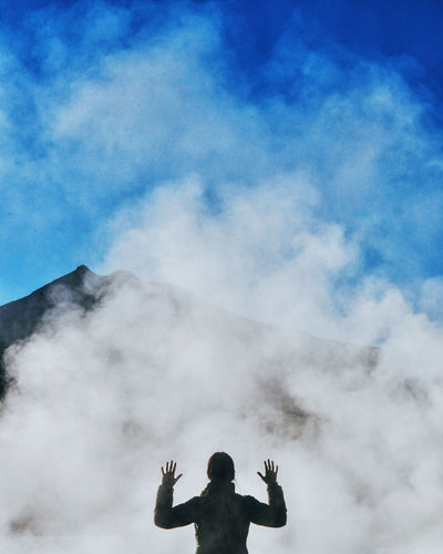 LOW ANGLE VIEW OF PERSON STANDING AGAINST CLOUDY SKY
