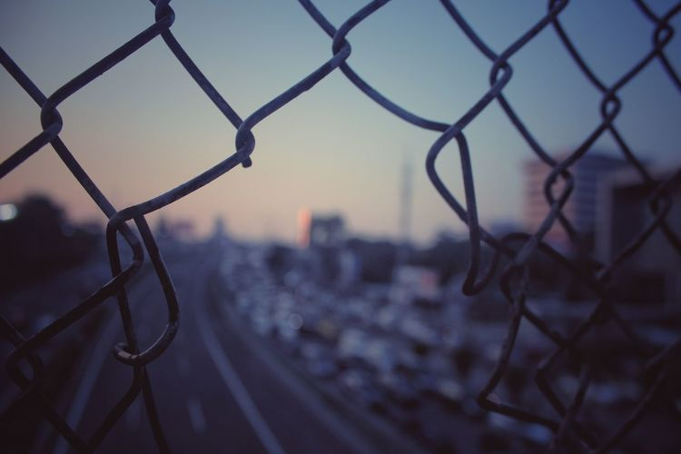 Close-Up Of Broken Chainlink Fence Against Cityscape