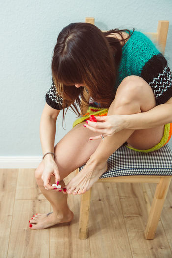 Woman painting toenails at home