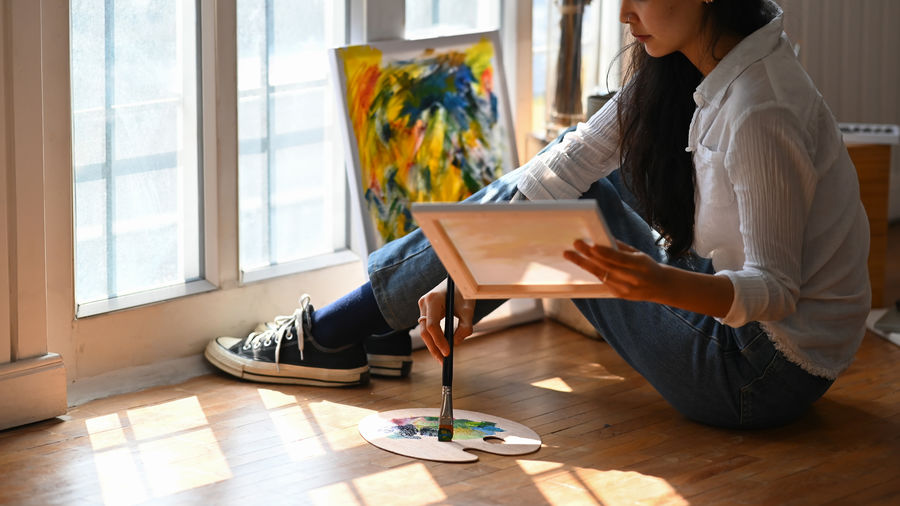 Low section of woman painting while sitting on floor