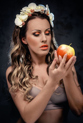 Beautiful seductive woman with apple, conceptual photo Apple Eden Eva Eve Make-up Myth Orchid Portrait Of A Woman Temptation Woman Beautiful Woman Brunnette Conceptual Flowers Forbidden Fruit Gorgeous Headband Holding Mythology Paradise Seduction Seductive Sensual_woman Sexygirl Sin