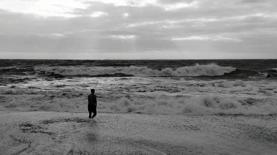 Man walking towards sea waves against sky