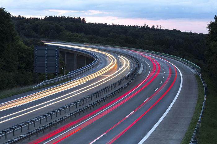 highway evening traffic Cars Lights Speeding Autobahn Bridge Evening Highway Motion No People Outdoors Road Speed Transportation Trucks