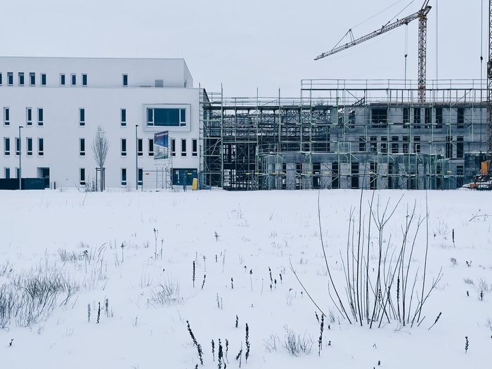 Snow covered field by buildings against sky