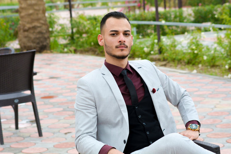 Portrait of confident businessman sitting on chair at patio