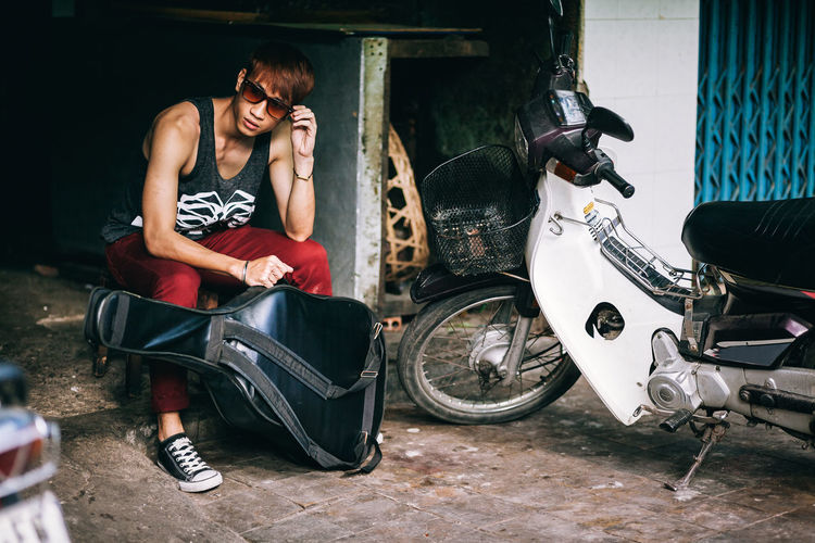 asian fashion model teenager in style sunglasses with guitar case Sitting One Person Casual Clothing Young Adult Leisure Activity Young Men Front View Adult Motobike ASIA Asian  Vietnamese Sunglasses Guitar Model Fashion Fashion Model Posing Authentic Man Male Bike Outdoors