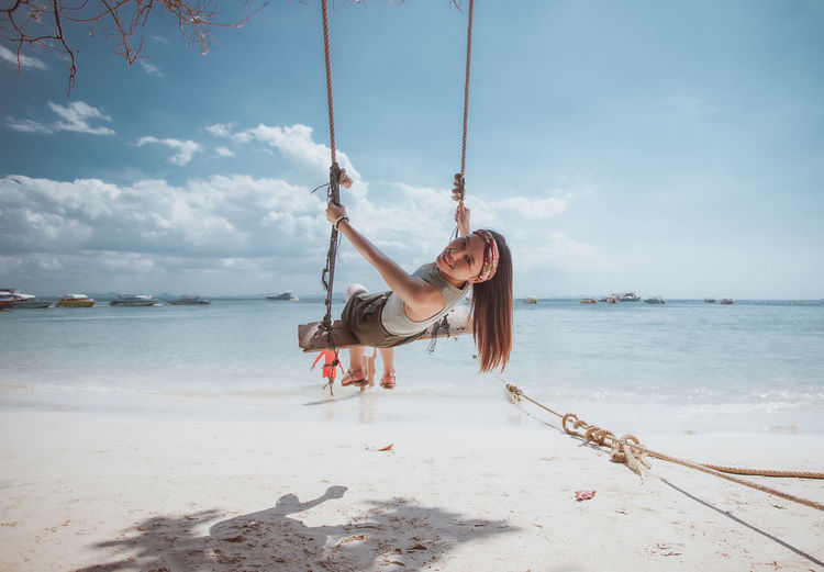Portrait of smiling young woman sitting on swing at beach against sky