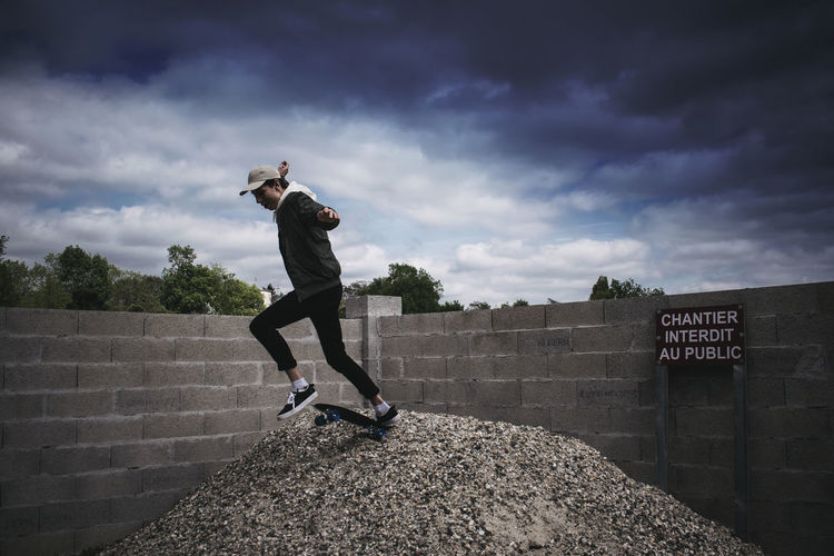 Full length of man skateboarding against cloudy sky