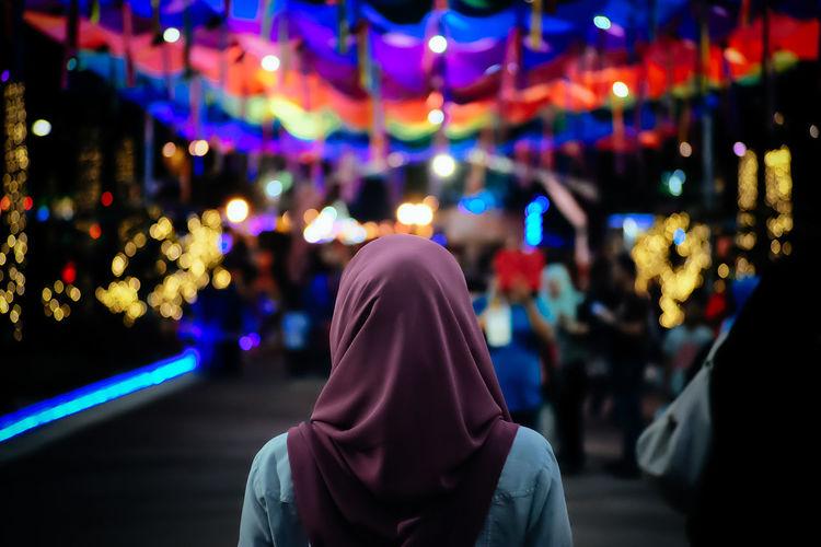 Rear View Of Woman Wearing Hijab Against Illuminated Lights At Market