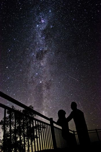 Silhouette of couple under starry sky