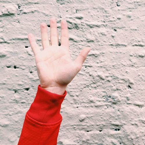Close-up of woman hand against wall
