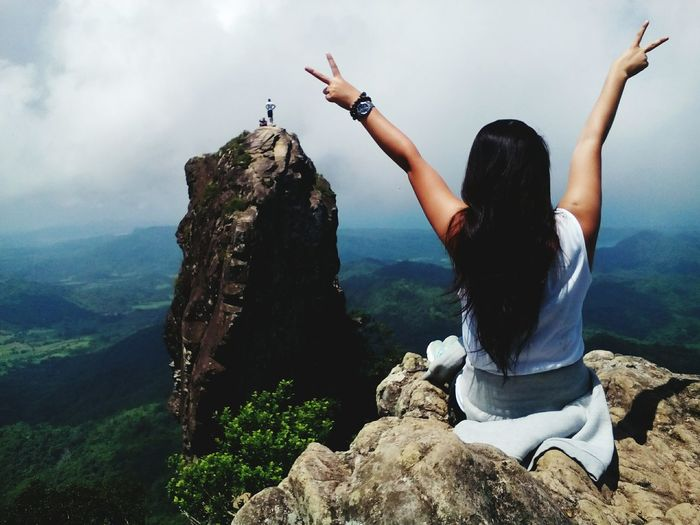 Rear view of woman showing peace sign on cliff