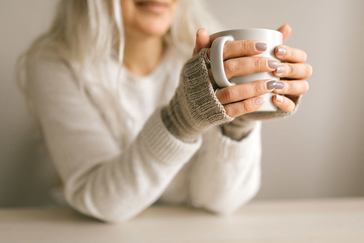 Midsection of woman holding coffee cup on table
