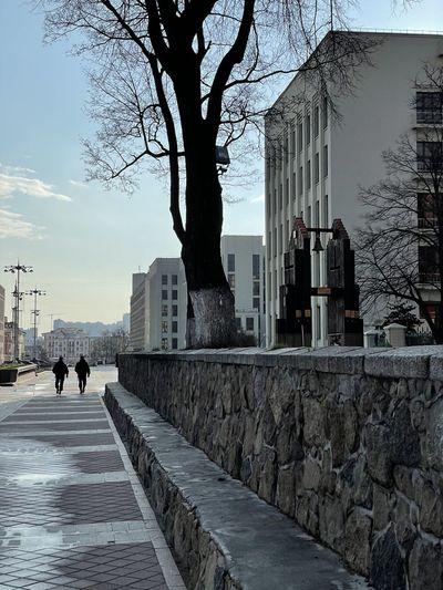 People walking on footpath in city against sky