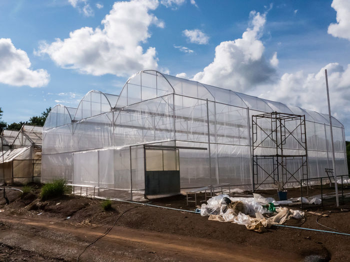 View Of Greenhouse On Field Against Cloudy Sky