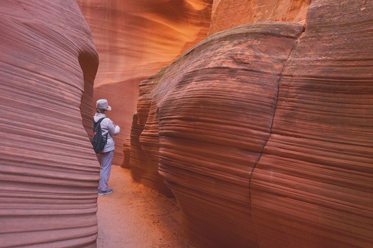 Rear view of man standing amidst rock formation