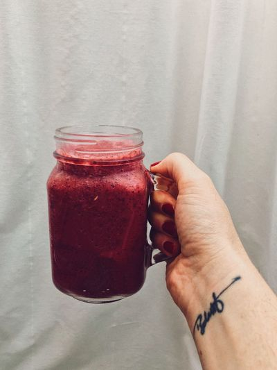 tattooed woman holding a vegan berry smoothie jar Breakfast Berry Smoothie Body Part Drink Finger Food Food And Drink Freshness Glass Hand Holding Human Body Part Human Hand Jar Lifestyles One Person Personal Perspective Real People Red Refreshment Smoothie Tattoo Unrecognizable Person Vegan Vegan Lifestyle