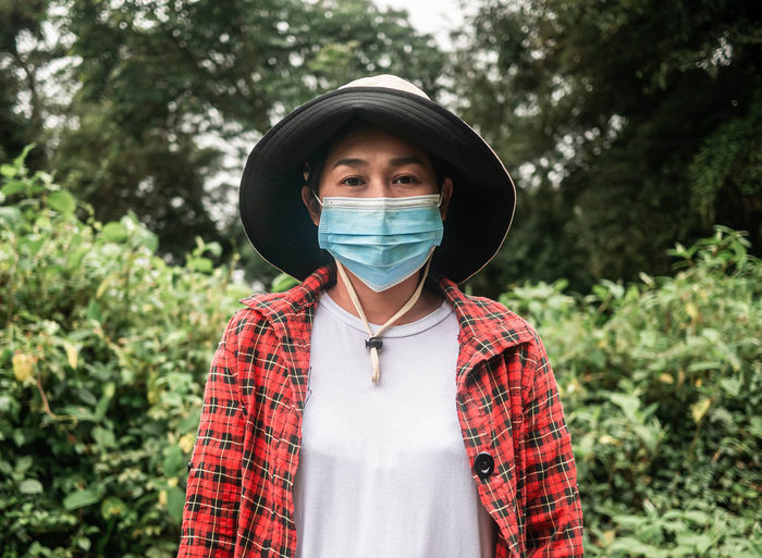 Portrait of woman wearing mask standing against plants